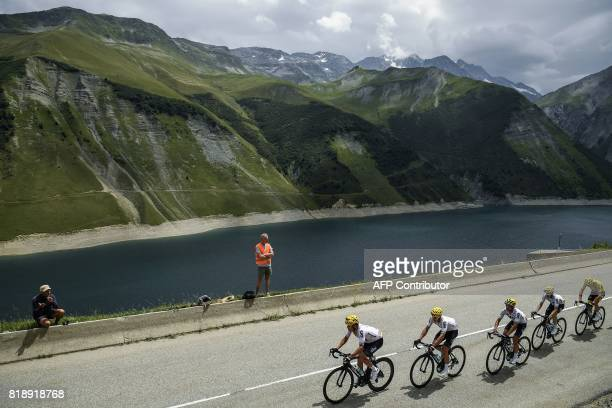 Great Britain's Christopher Froome wearing the overall leader's yellow jersey rides behind his teammates past a lake during the 183 km seventeenth...