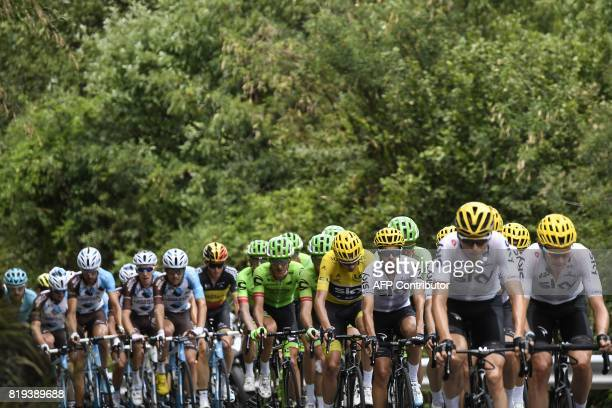 Great Britain's Christopher Froome wearing the overall leader's yellow jersey rides in the pack behind his temmates during the 1795 km eighteenth...