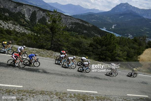 Great Britain's Christopher Froome wearing the overall leader's yellow jersey and Italy's Fabio Aru ride in the pack during the 2225 km nineteenth...
