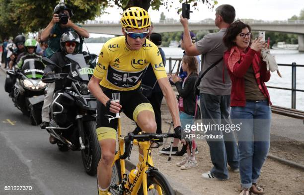 TOPSHOT Great Britain's Christopher Froome wearing the overall leader's yellow jersey drinks champagne as he takes the start of the 103 km...