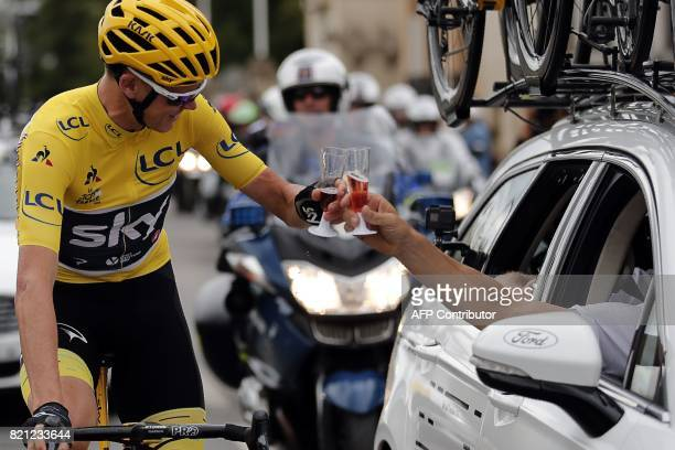 Great Britain's Christopher Froome wearing the overall leader's yellow jersey toats with champagne as he takes the start of the 103 km twentyfirst...