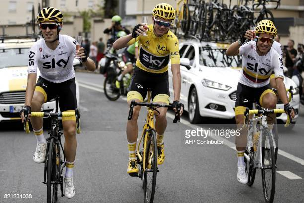 Great Britain's Christopher Froome wearing the overall leader's yellow jersey and Spain's Mikel Nieve and Colombia's Sergio Henao drink champagne as...