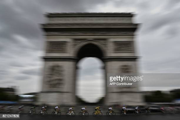 TOPSHOT Great Britain's Christopher Froome wearing the overall leader's yellow jersey rides past the Arc de Triomphe during the 103 km twentyfirst...