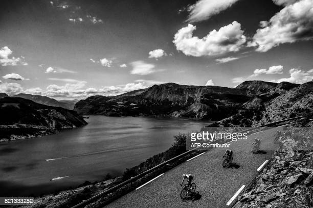 Great Britain's Christopher Froome wearing the overall leader's yellow jersey rides past a lake during the 1795 km eighteenth stage of the 104th...