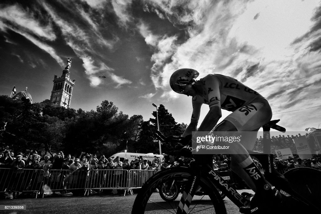 Great Britain's Christopher Froome, wearing the overall leader's yellow jersey, rides past the Notre-Dame de la Garde basilica (L) as he competes in a 22,5 km individual time-trial, the twentieth stage of the 104th edition of the Tour de France cycling race on July 22, 2017 in and around Marseille, southern France. /