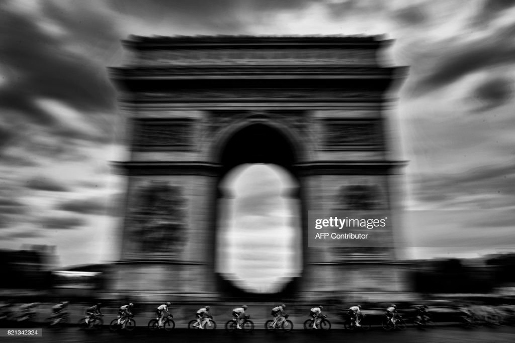 Great Britain's Christopher Froome (C), wearing the overall leader's yellow jersey, rides past the Arc de Triomphe during the 103 km twenty-first and last stage of the 104th edition of the Tour de France cycling race on July 23, 2017 between Montgeron and Paris Champs-Elysees. /