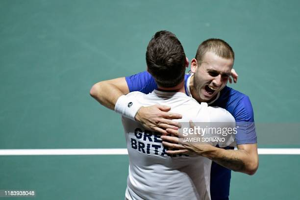 Great Britain's Daniel Evans celebrates with Great Britain's captain Leon Smith after winning the singles quarterfinal tennis match against Germany's...