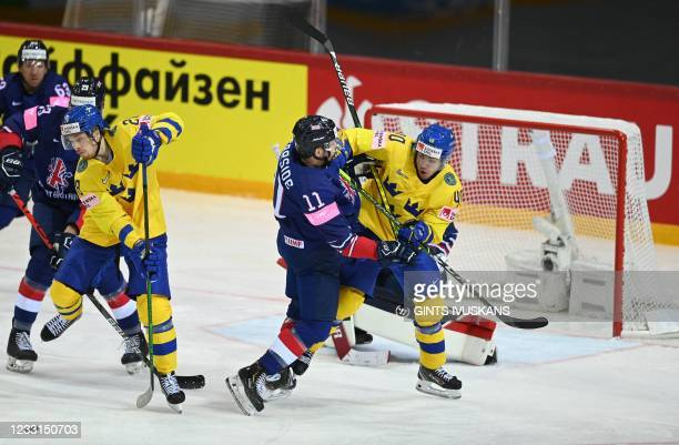 Great Britain's defender Mark Garside and Sweden's forward Andreas Wingerli vie during the IIHF Men's Ice Hockey World Championships preliminary...