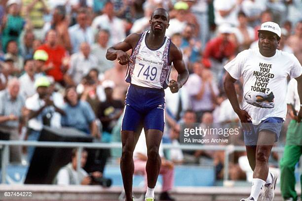 Great Britain's Derek Redmond limps around the track towards the finish line after tearing his hamstring as his dad Jim races after him to offer help...