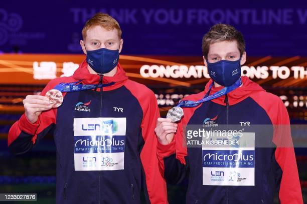 Great Britain's Duncan Scott poses with his silver medal past bronze medallist Great Britain's Thomas Dean on the podium of the Mens 200m Freestyle...
