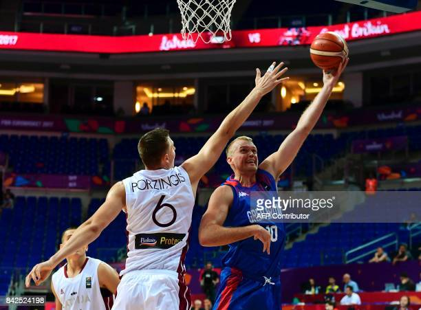 Great Britain's forward Dan Clark tries to score a basket next to Latvia's forward Kristaps Porzingis during FIBA Eurobasket 2017 men's group D...