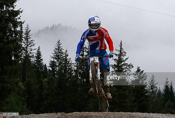 Great Britain's Gee Atherton jumps as he competes during the men's elite downhill official timed session as part of the 2012 UCI Mountain Bike and...