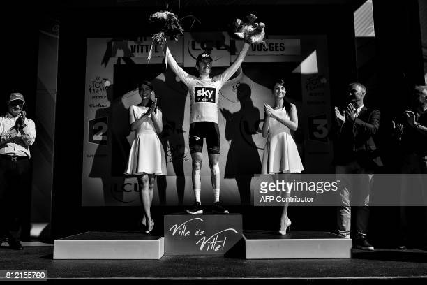 Great Britain's Geraint Thomas celebrates his overall leader yellow jersey on the podium at the end of the 2075 km fourth stage of the 104th edition...