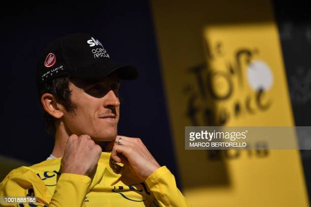 Great Britain's Geraint Thomas puts on the overall leader's yellow jersey on the podium after winning the twelfth stage of the 105th edition of the...