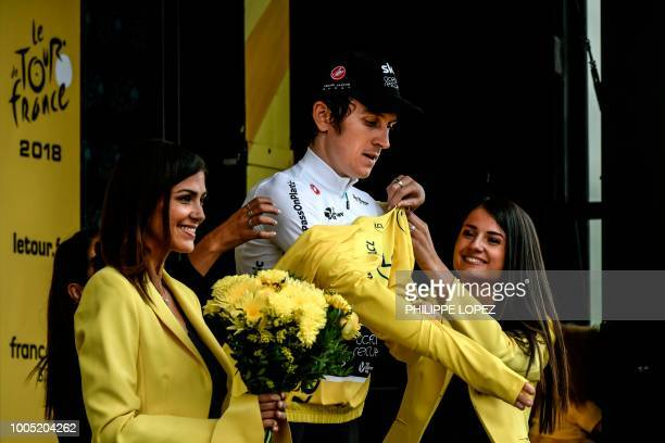 Great Britain's Geraint Thomas puts on the overall leader's yellow jersey on the podium after the 17th stage of the 105th edition of the Tour de...