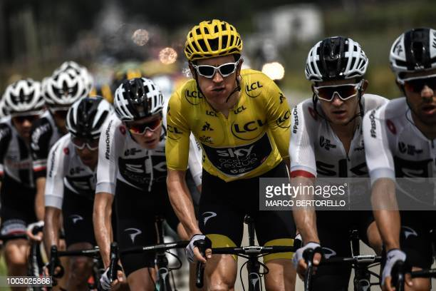 TOPSHOT Great Britain's Geraint Thomas wearing the overall leader's yellow jersey eats a snack as he rides in the pack with his Great Britain's Team...