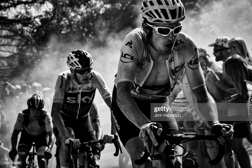 Great Britain's Geraint Thomas (R), wearing the overall leader's yellow jersey, and Great Britain's Christopher Froome (C) rides through the so-called 'Dutch Corner' in the ascent to l'Alpe d'Huez during the twelfth stage of the 105th edition of the Tour de France cycling race, between Bourg-Saint-Maurice - Les Arcs and l'Alpe d'Huez, on July 19, 2018. (Photo by JEFF PACHOUD / AFP) / BLACK