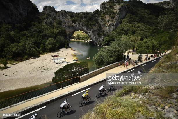 Great Britain's Geraint Thomas wearing the overall leader's yellow jersey and his seven Great Britain's Team Sky cycling team teammates cycle past...