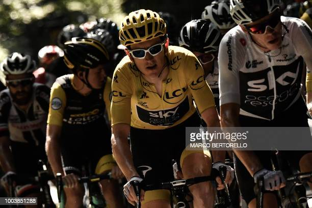 Great Britain's Geraint Thomas , wearing the overall leader's yellow jersey, and Great Britain's Christopher Froome ride in the pack during the 15th...