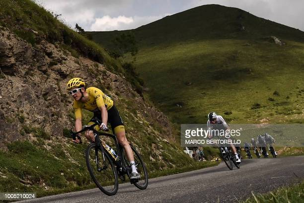 TOPSHOT Great Britain's Geraint Thomas wearing the overall leader's yellow jersey and Great Britain's Christopher Froome ride downhill during the...