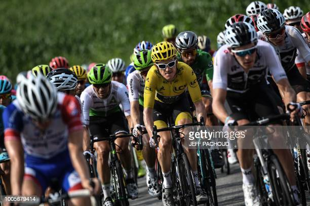 Great Britain's Geraint Thomas wearing the overall leader's yellow jersey and Great Britain's Christopher Froome ride in the pack during the 18th...