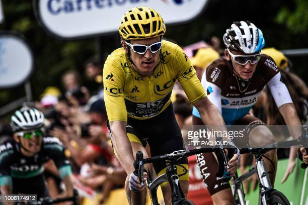 Great Britain's Geraint Thomas , wearing the overall leader's yellow jersey, and France's Romain Bardet cross the finish line to place 2nd and third...