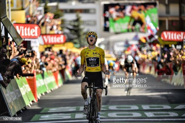 TOPSHOT Great Britain's Geraint Thomas wearing the overall leader's yellow jersey celebrates as he crosses the finish line to win the twelfth stage...