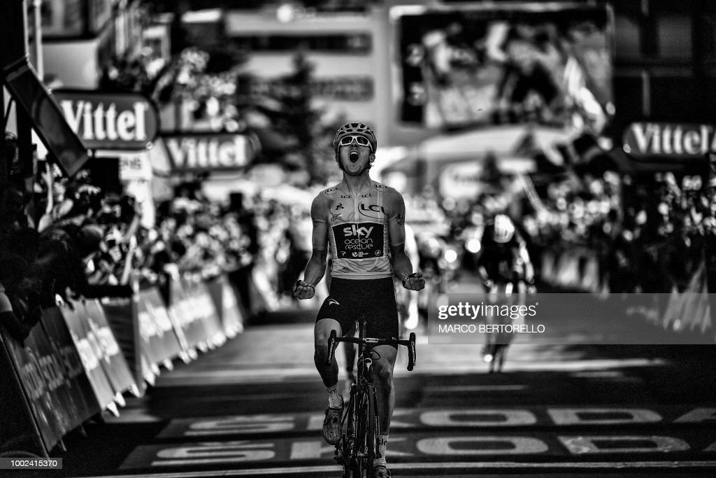 Great Britain's Geraint Thomas, wearing the overall leader's yellow jersey, celebrates as he crosses the finish line to win the twelfth stage of the 105th edition of the Tour de France cycling race, between Bourg-Saint-Maurice - Les Arcs and l'Alpe d'Huez, on July 19, 2018. (Photo by MARCO BERTORELLO / AFP) / BLACK