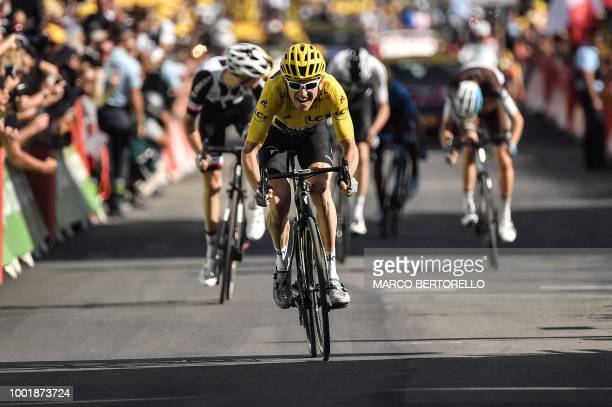 Great Britain's Geraint Thomas, wearing the overall leader's yellow jersey, rides on his way to cross the finish line to win the twelfth stage of the...