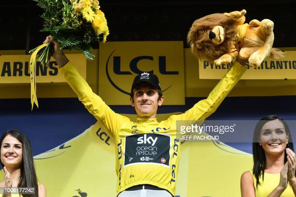 Great Britain's Geraint Thomas wearing the overall leader's yellow jersey celebrates on the podium after the 19th stage of the 105th edition of the...