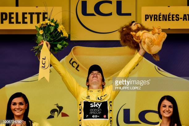 TOPSHOT Great Britain's Geraint Thomas wearing the overall leader's yellow jersey celebrates on the podium after the 20th stage of the 105th edition...