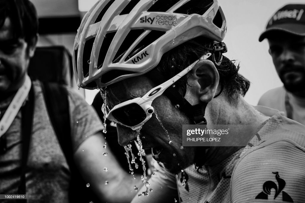 Great Britain's Geraint Thomas, wearing the overall leader's yellow jersey, refreshes himself after winning the twelfth stage of the 105th edition of the Tour de France cycling race, between Bourg-Saint-Maurice - Les Arcs and l'Alpe d'Huez, on July 19, 2018. (Photo by PHILIPPE LOPEZ / AFP) / BLACK