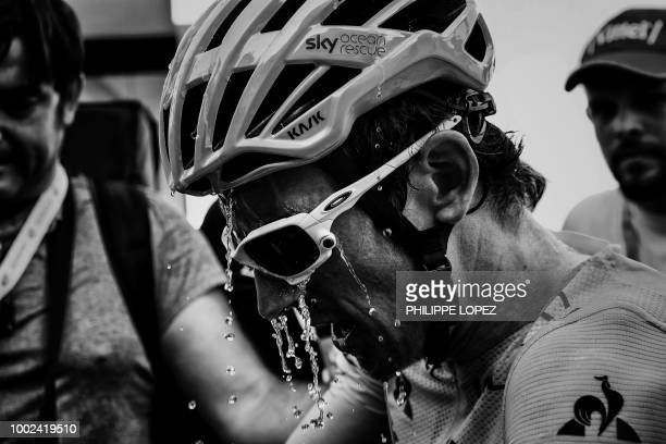 Great Britain's Geraint Thomas wearing the overall leader's yellow jersey refreshes himself after winning the twelfth stage of the 105th edition of...
