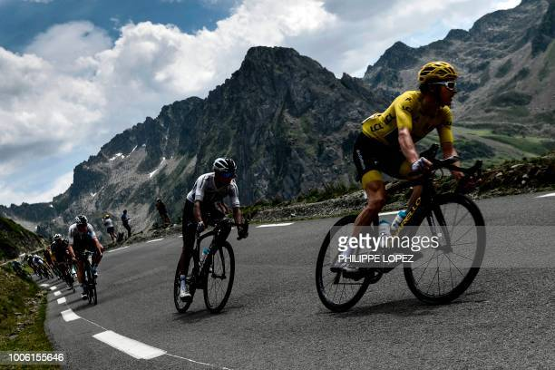 Great Britain's Geraint Thomas, wearing the overall leader's yellow jersey, Colombia's Egan Bernal and Great Britain's Christopher Froome ride down...