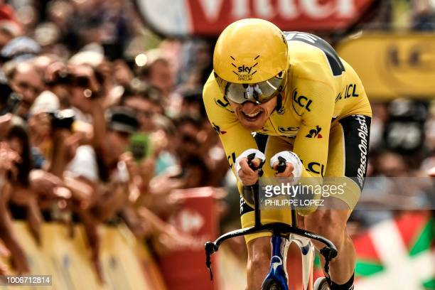 Great Britain's Geraint Thomas wearing the overall leader's yellow jersey crosses the finish line to place third of the 20th stage of the 105th...