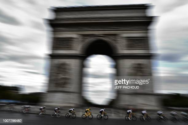 TOPSHOT Great Britain's Geraint Thomas wearing the overall leader's yellow jersey rides past the Arc de triomphe monument during the 21st and last...