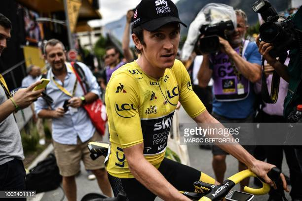 Great Britain's Geraint Thomas wearing the overall leader's yellow jersey celebrates on the podium under the eye of French Prime Minister Edouard...