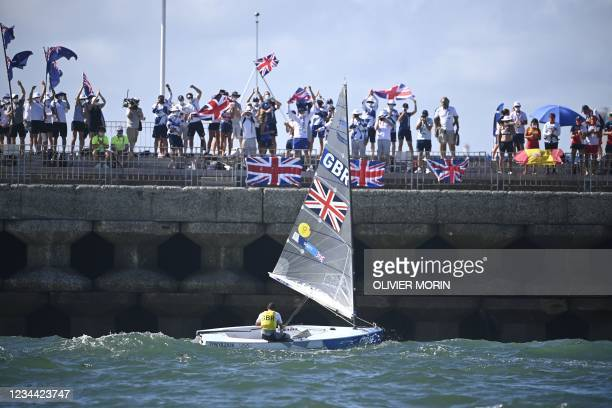 Great Britain's Giles Scott celebrates after the men's one-person dinghy finn race during the Tokyo 2020 Olympic Games sailing competition at the...