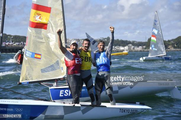 Great Britain's Giles Scott , Spain's Joan Caedona and Hungary's Zsombor Berecz celebrate after the men's one-person dinghy finn race during the...