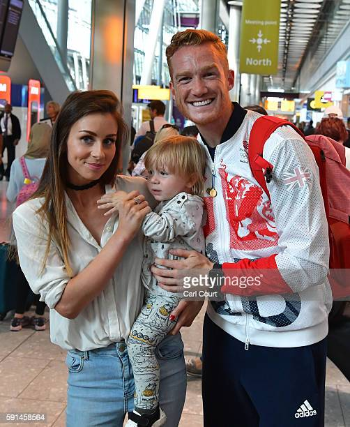 Great Britain's Greg Rutherford poses for a photograph with his partner Susie Verrill and son Milo after arriving on a British Airways flight from...