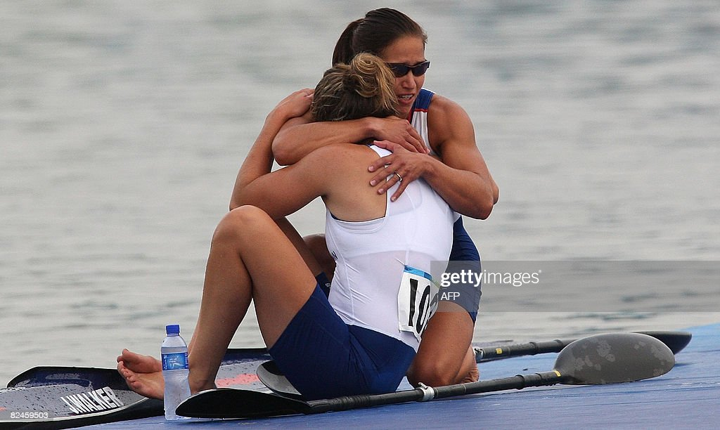 Great Britain's Jessica Walker (L,back to camera ) is consoled by teammate Anna Hemmings after failing to qualify in the 2008 Beijing Olympic Games Women's Kayak K2 500m flatwater heats event at the Shunyi Rowing and Canoeing Park in Beijing on August 19, 2008. AFP PHOTO / Manan VATSYAYANA