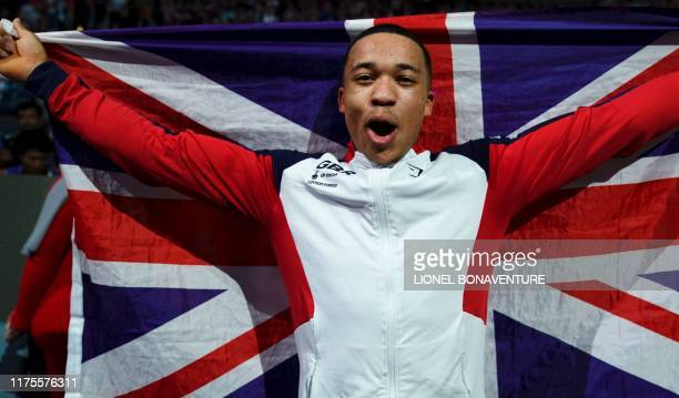 Great Britain's Joe Fraser celebrates with his national flag after winning the parallel bars apparatus final at the FIG Artistic Gymnastics World...