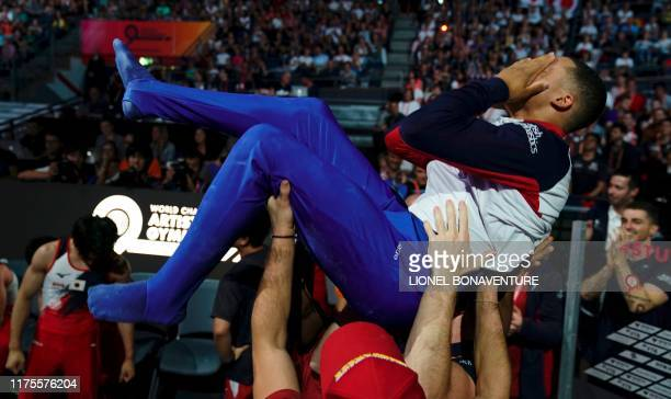 Great Britain's Joe Fraser celebrates with his team after winning the parallel bars apparatus final at the FIG Artistic Gymnastics World...