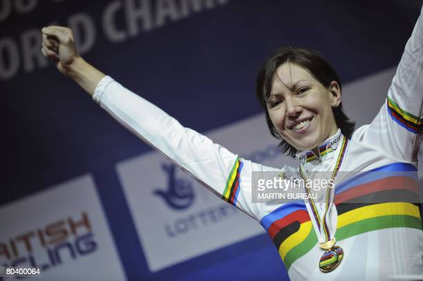 Great Britain's Rebecca Romero gestures as she poses with her gold medal on the podium after winning the women's individual pursuit final in the UCI...