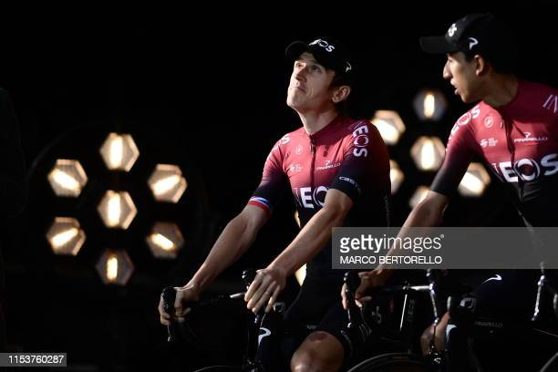 Great Britain's rider Geraint Thomas of Great Britain's Team Ineos poses with teammates on stage during the team presentation ceremony at the...