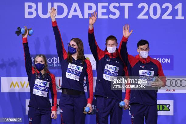 Great Britain's team members Abbie Wood, Freya Anderson, Thomas Dean and James Guy wave as they pose with their gold medals on the podium of the...
