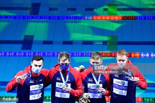Great Britain's team members celebrate their silver medals on the podium of the Mens 4x100m Freestyle Relay Swimming event during the LEN European...