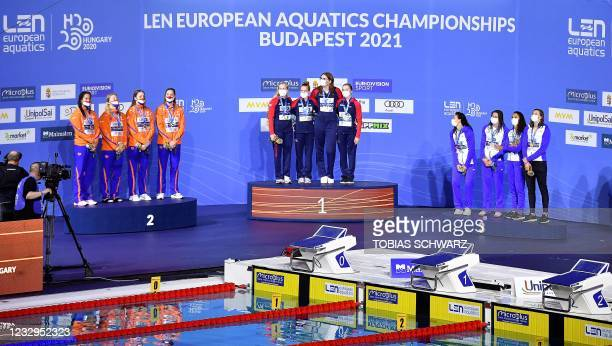 Great Britain's team members pose with their gold medals past silver medallist Netherlands and bronze medallist France on the podium of the Womens...