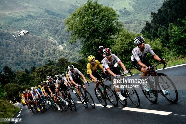 TOPSHOT Great Britain's Team Sky cycling team teammates with Great Britain's Geraint Thomas wearing the overall leader's yellow jersey ascend with...