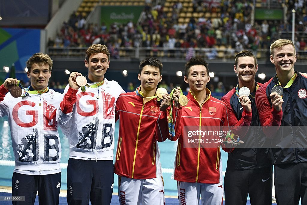 Great Britain's Thomas Daley and Great Britain's Daniel Goodfellow (L, bronze), China's Chen Aisen and China's Lin Yue (C, gold) and US David Boudia and US Steele Johnson (R, silver) celebrate during the podium ceremony for the Men's Synchronised 10m Platform contest during the diving event at the Rio 2016 Olympic Games at the Maria Lenk Aquatics Centre in Rio de Janeiro on August 8, 2016. / AFP / Martin BUREAU